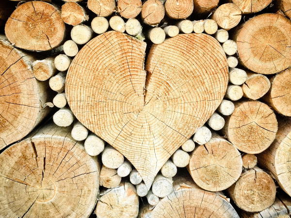 A wood pile, focused on a wooden heart
