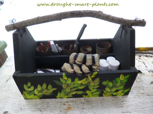 Twig Handled Trug containing an assortment of plant collecting tools...